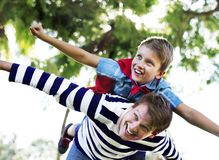 Superhero boy flying on the back of his dad Royalty Free Stock Photo