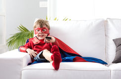Superhero boy watching tv. Cute boy with super hero costume sitting on living room sofa and watching tv Stock Image
