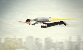 Superhero business man flying with jet pack rocket above the cit Stock Photo