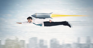 Superhero business man flying with jet pack rocket above the cit Stock Images