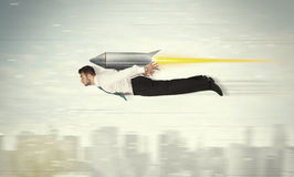 Superhero business man flying with jet pack rocket above the cit Stock Photos
