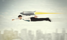 Superhero business man flying with jet pack rocket above the cit Royalty Free Stock Image