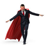A superhero in a business suit and a red cape keeping his balance on an invisible rope. Royalty Free Stock Photo