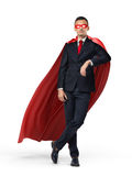 A superhero in a business suit and a red cape leaning on an invisible object on white background. Believing in yourself. Business presentation. Success and Royalty Free Stock Photography