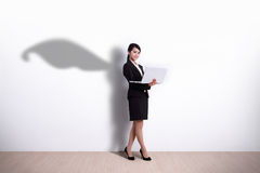 Superhero Business Woman with computer. Superhero business woman using laptop computer with white wall background, great for your design or text, asian stock photo