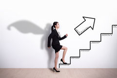 Superhero business woman with stair stock photography