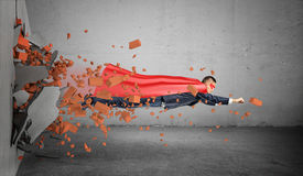 A superhero businessman in a cape flying right through the wall leaving rubble behind him. Stock Photos