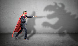 A superhero businessman fighting off a dragon shadow on concrete background. Stock Photo