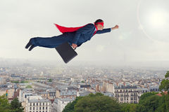 Superhero businessman flying above a city Royalty Free Stock Photo