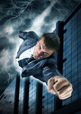 Superhero businessman flying over downtown royalty free stock photography