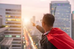Superhero businessman looking at city skyline at sunset. the con stock image