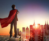 Superhero businessman looking at city. Skyline at sunset. the concept of success, leadership and victory in business Royalty Free Stock Image