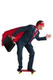Superhero businessman riding a skateboard Stock Images
