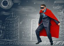 Superhero. Businessman superhero in red cloak and mask is walking on the building roof and looking around royalty free stock photo
