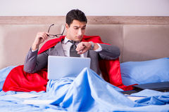 The superhero businessman working from his bed Stock Photo