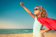 Superhero child on the beach. Summer vacation concept royalty free stock image