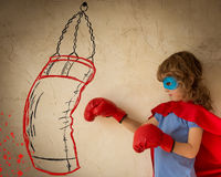 Superhero. Child dressed in red cape, boxing gloves and blue mask against grunge wall background stock photos