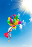 Superhero child playing with bright multicolor balloons. Outdoor. Kid having fun against blue sky background. Summer vacation and travel concept royalty free stock photography