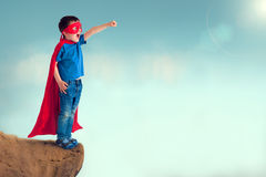 Superhero child. Standing on a cliff with cape and mask Stock Photos
