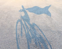 Superhero Child. Wearing a cape riding a bicycle as a cast shadow on a road pretending to be a powerful hero as a metaphor and symbol of youth and childhood Royalty Free Stock Photo