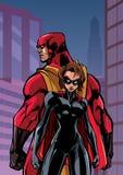 Superhero Couple in City. Superhero couple standing back to back on city background Royalty Free Stock Image
