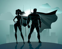 Superhero Couple: Male and female superheroes, posing in front o vector illustration