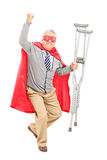Superhero with crutches gesturing happiness Stock Photos