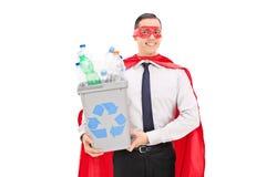 Superhero die een kringloopbak houden Stock Foto