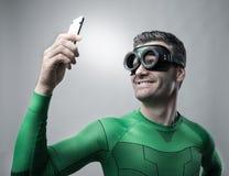 Superhero die een selfie met een smartphone nemen stock foto