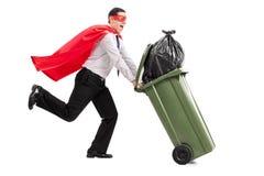 Superhero die een volledige vuilnisbak duwen Stock Fotografie