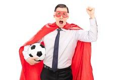 Superhero die en een voetbal toejuichen houden Royalty-vrije Stock Afbeeldingen