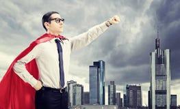 Superhero die zich voor een donkere stad bevinden Stock Fotografie