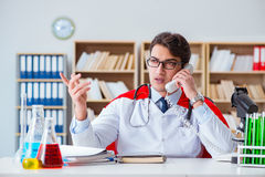 The superhero doctor working in the hospital lab Royalty Free Stock Image