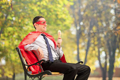 Superhero enjoying an ice cream seated on bench. In park Stock Images