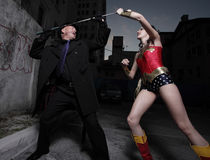 Superhero and evil villain fighting Stock Image