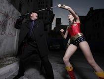 Superhero and evil villain fighting Stock Image