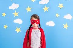 Superhero för lekar för litet barn Unge på bakgrunden av den ljusa blåa väggen med vitmoln och stjärnor Flickamaktbegrepp Royaltyfri Foto