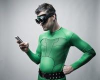 Superhero gebruikend een smartphone Stock Fotografie