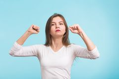 Superhero girl. Confident young woman isolated on blue background.  royalty free stock images
