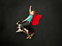 Superhero girl riding her dog Royalty Free Stock Photo