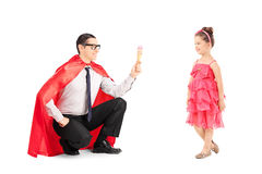 Superhero giving an ice cream to a little girl Stock Images