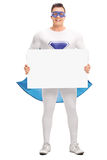Superhero holding a blank signboard. Full length portrait of a male superhero holding a blank signboard and looking at the camera isolated on white background royalty free stock photography