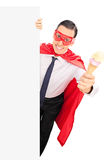Superhero holding an ice cream behind a panel Royalty Free Stock Image