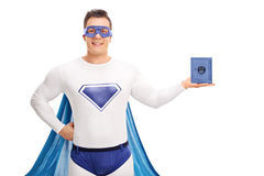 Superhero holding a small blue safe. Superhero in a white and blue costume holding a small blue safe and looking at the camera isolated on white background Stock Photos