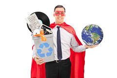 Superhero holding the world and a recycle bin. Full of old stuff isolated on white background, earth image in public Domain and furnished by NASA stock images