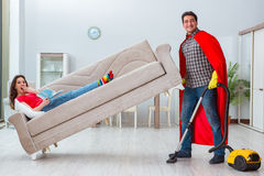 The superhero husband helping his wife at home Royalty Free Stock Photo
