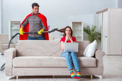 The superhero husband helping his wife at home Stock Photography