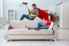 The superhero husband helping his wife at home Stock Image
