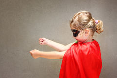 Superhero kid against blue sky background. Royalty Free Stock Photo