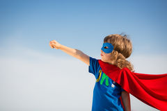 Superhero kid. Against blue sky background. Girl power concept Royalty Free Stock Photo